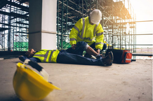 Hurt construction worker being given first aid