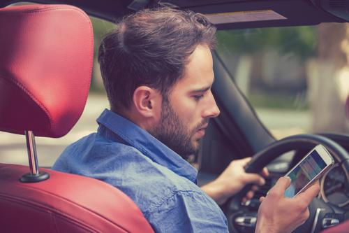 A man looking at his phone while driving.
