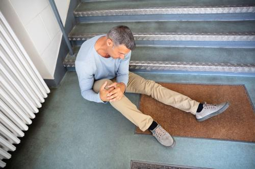 A man with a knee injury after falling down a flight of stairs.