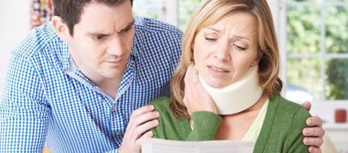A woman with a neck injury looking at an insurance settlement offer.