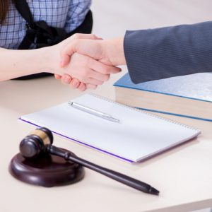 Injured client shaking hands with Taunton workers' compensation lawyer in office.