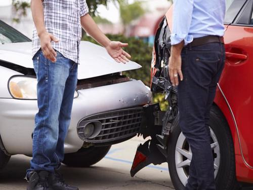 Two drivers exchanging information after a car accident.