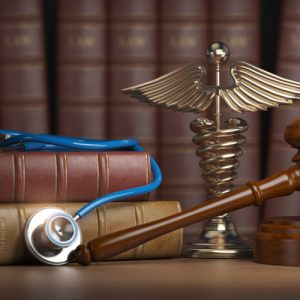 Image is of law book, gavel, and stethoscope on the desk of a Brockton bicycle accident lawyer