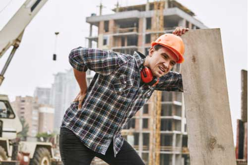 Construction worker rubbing hurt back, concept of Bridgewater workers' compensation lawyer