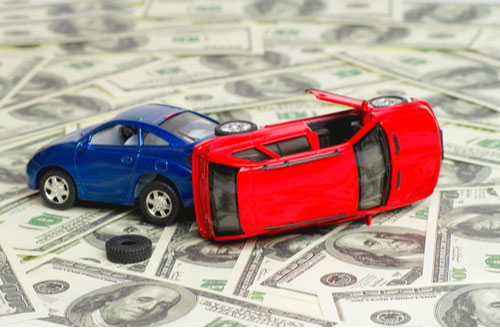 Toy cars crashed on top of money, Pembroke car accident lawyer concept