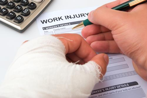 Hurt employee fills out work injury report, Walpole workers' compensation lawyer concept