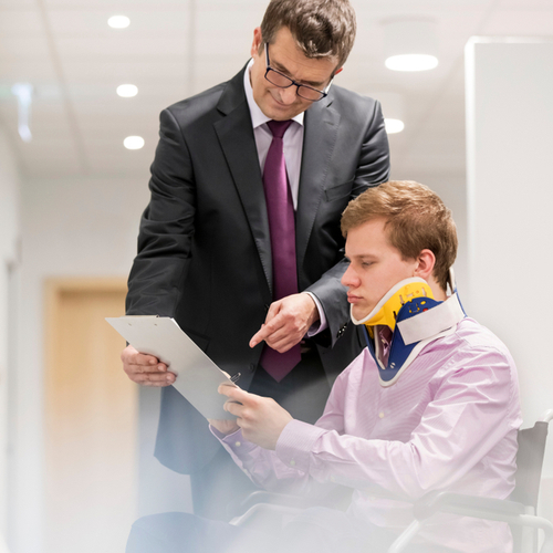 This is an image of an injured man in a wheelchair speaking to a Norwood personal injury lawyer