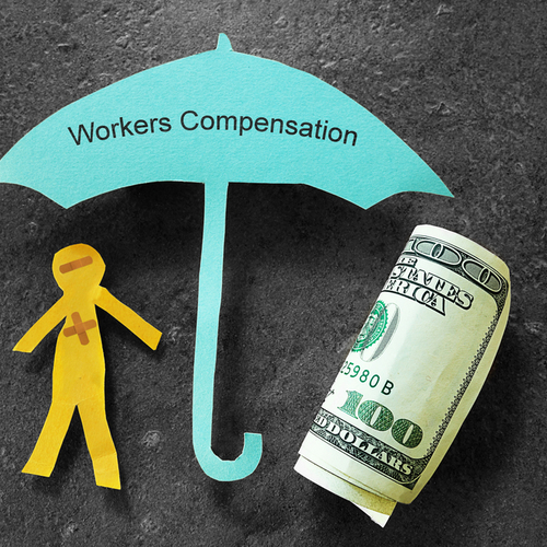 This is an image of a paper cutout of a man and money being covered by an umbrella that say workers' compensation in the office of a Norwood workers' compensation lawyer